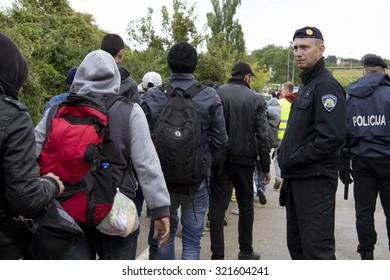 SID, SERBIA - SEPTEMBER 28, 2015: Croatian policemen watching refugees crossing the Serbo-Croatian border between the cities of Sid (Serbia) and Bapska (Croatia)