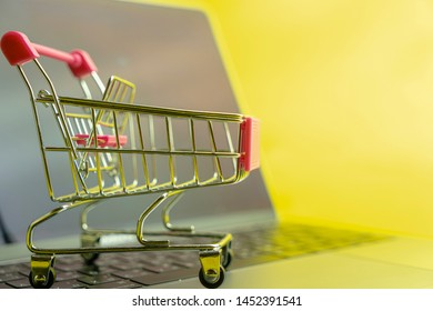 Sid view of Trolly cart on laptop keyboard with yellow space copy
