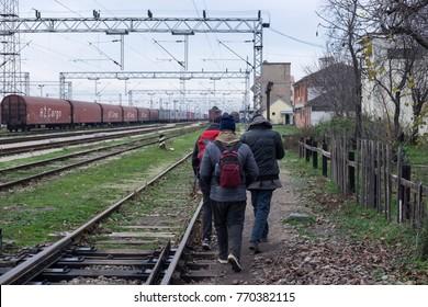 Sid, western Serbia. 11/22/17. North African migrants walk along the train tracks.