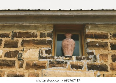 Side of abandoned home with vase in Window
