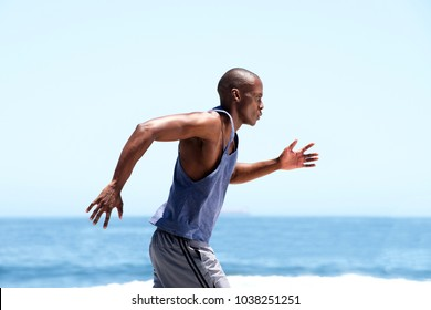 Side of african american male runner outside by sea
