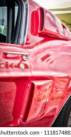 The side air scoops of a sixties American sports car in red.