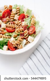 Side angle of BLT pasta salad with crispy bacon, grape tomatoes, green leafy lettuce and fresh mozzarella in white bowl with blue striped linen.