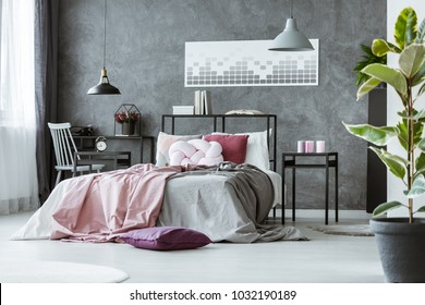 Side angle of gray bedroom interior with pink sheets on the bed, metal bedhead with books on it and nightstands