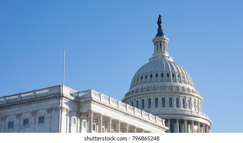 Side angle photo of The Capitol Building in Washington, D.C. with a bright blue sky.