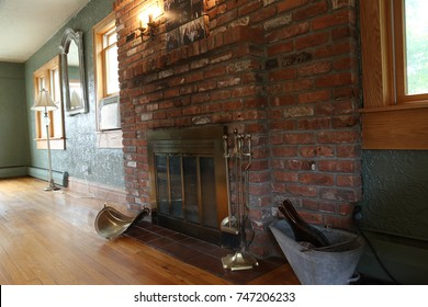Side angle of a red brick fireplace in a living space.