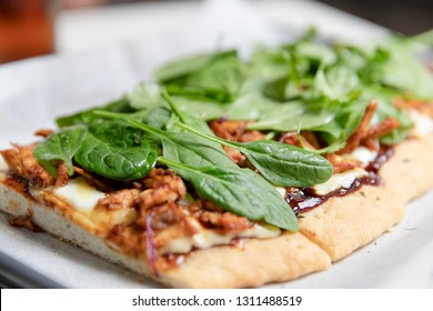 Side angle shot of a barbeque chicken topped with spinach flatbread pizza. Fresh homemade flatbread pizza