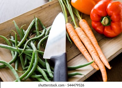 Side angle shot of chef's knife illuminated on wooden platter with fresh green beans, raw carrots, and red and orange bell pepper.