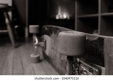 Side angle of skateboard laying on wood floor with a fire burning in the fireplace behind it