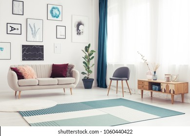 Side angle view of a modern living room with blue rug, elegant sofa and big window