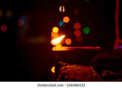 Side angle view of terracotta oil lamp or diya lit during deepavali or diwali festival with rice lights or diwali lights on edge.Happy diwali