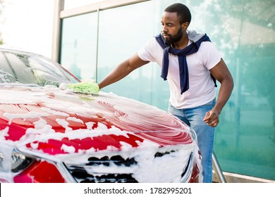 Side angle view of young handsome African man washing his red car hood with green sponge and detergent at self car wash outdoor