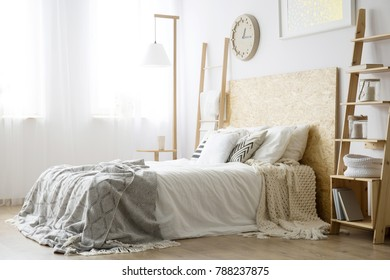 Side angle of white bed with wooden bedhead and gray blanket in bright bedroom