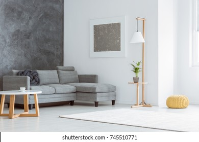 Side angle of white minimalist living room with gray accents, painting, sofa, lamp, scandinavian coffee table and window