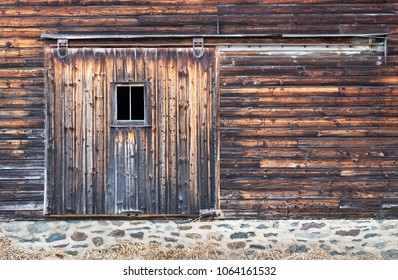 Side of Barn showing Distressed Board Door with Window and Stone Wall Foundation.