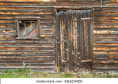 Side of Barn showing Distressed Board Door with Corrugated Metal and Wood in Window.