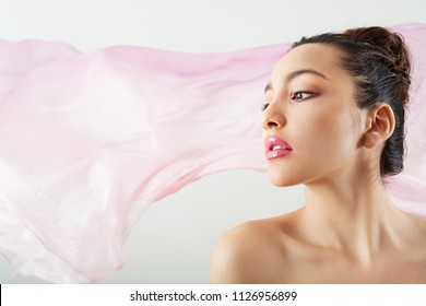 Side beauty portrait of ethnic asian young woman with attitude and flawless skin against pink floating fabric background, studio indoors. Cosmetics healthy beautiful female, dreamy ethereal lifestyle.