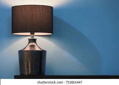 Side bed lamp with with brown cloth lampshade in a blue wall bedroom.