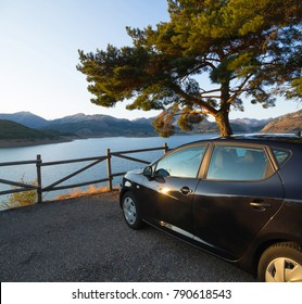 Side black car, parked in a rest area, viewpoint, or lookout road, in the shade of a tree and a fence of wooden posts. Against a backdrop of mountains and lake or swamp viaje; turismo; transporte; ave