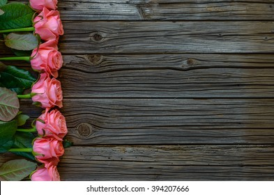 Side border of beautiful fresh pink roses symbolic of love and romance on a rustic wood background for Valentines Day, Mothers Day, anniversary or wedding