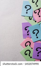 Side border of colorful question marks on multicolored paper in a random scatter over grey with copy space