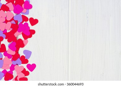 Side border of colorful Valentines Day paper hearts against a white wood background