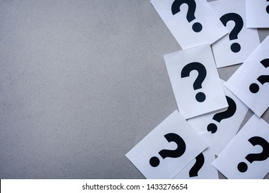 Side border of printer question marks on white paper in a random arrangement over grey with copy space