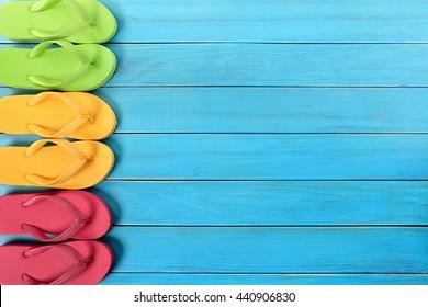 Side border row of summer flip flops on blue beach wood background