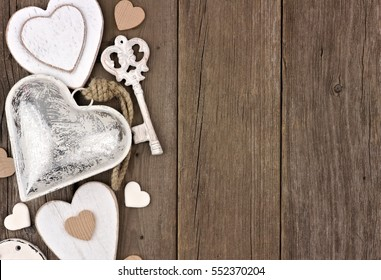 Side border of white and silver hearts and love themed decor on a rustic wooden background