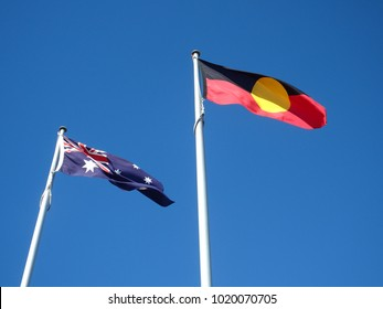 Side by side flying in the wind, the flags of the commonwealth of Australia and the first australians aboriginal flag