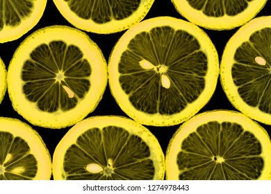 Side by side lemon slices are illuminated from below.