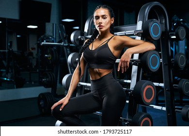 Side close up of female bodybuilder with long braids posing near stand with sports equipment. Srtong woman with muscular body leaning on barbells in gym in dark atmosphere, looking at camera.