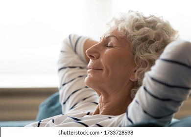 Side close up head shot view tranquil calm middle aged hoary woman crossed hands behind head, relaxing on cozy sofa alone. Peaceful mindful mature senior grandmother daydreaming meditating at home.