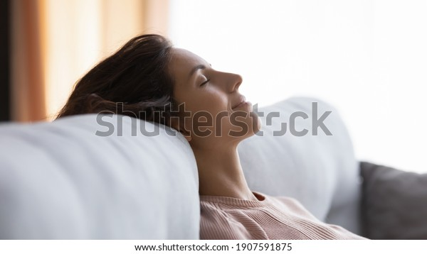 Side close up head shot view tranquil young pretty woman sleeping lying on comfortable couch, enjoying peaceful quiet time napping alone at home, having pleasant dreams or meditating indoors.