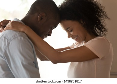 Side close up image profile faces african couple in love touching foreheads, female hugs beloved man neck lovers closed eyes enjoy moment of closeness, sincere feelings, tenderness and caress concept