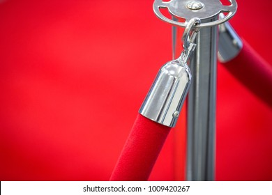Side close up on a chrome clip and stanchion with red velvet ropes, and formal red carpet background