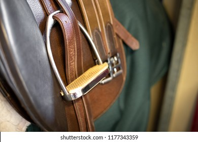 Side close up on the metal foot stirrup on a brown leather horse saddle