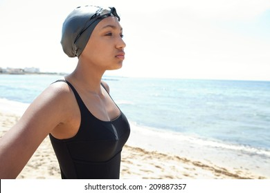 Side close up portrait of a healthy african american young woman swimmer on a beach with goggles and a swimming cap, training outdoors feeling strong and confident. Sport lifestyle outdoors.