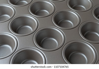 Side close view of a new mini muffin pan illuminated with natural light.