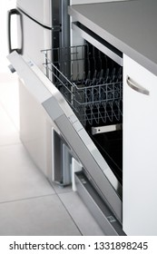 Side close up view open door of new clean empty dishwasher near fridge, mechanical device for cleaning dishware and cutlery automatically, concept modern home, easy comfortable usage, vertical image