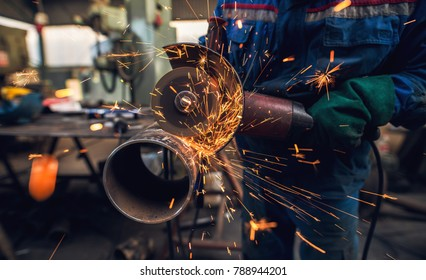 Side close up view of professional hardworking man in uniform cuts metal pipe sculpture with a large electric grinder while sparks flying in the industrial fabric workshop or garage.