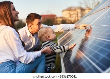 Nahaufnahme einer jungen modernen Familie mit einem kleinen Sohn, der sich an einem sonnigen Tag mit Solarpaneelen vertraut macht, grünes Alternativenergiekonzept