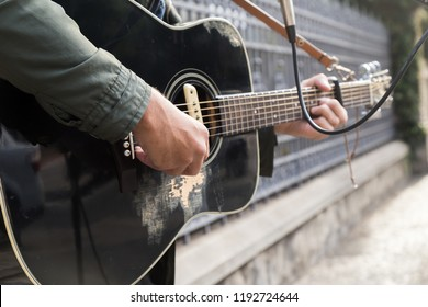 A side and close-up view in the afternoon of a mixed race man playing your guitar in the street. Music, culture, urban and people as a concept