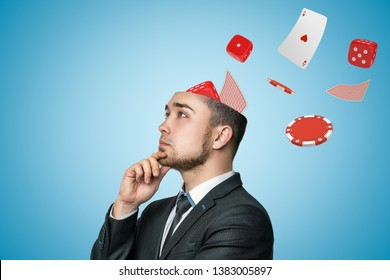 Side close-up of young handsome businessman rubbing chin, upper part of head cut off, with cards, dice and casino chips flying out. Casino games. Gambling business. Addicted to gambling.