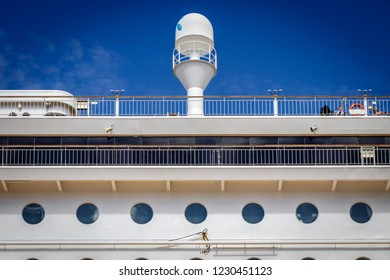 The side of a cruise ferry in the harbor of Kiel. Many windows of the hotel rooms and a radar on a floating city.  A cruise ship is a  supersized pollution problem.