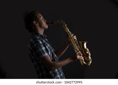 Side dark shot of a young musician blowing in the saxophone.