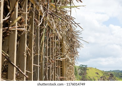 Side detail in the foreground of a trailer for transporting sugar cane. In the background, the sky is cloudy and several plants in various shades of green. Zona da mata sul de Pernambuco. Brazil.