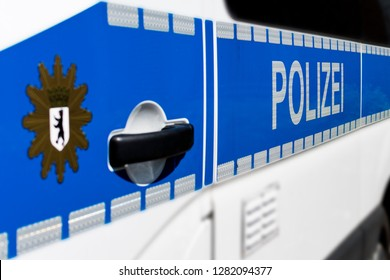 "Side detail view of a Berlin police car with the word ""Polizei"" and the blurred Berlin city coat of arms in the foreground"