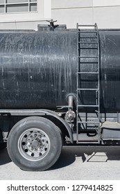 Side of a dirty black asphalt distributor truck with metal ladder. Vertical composition.