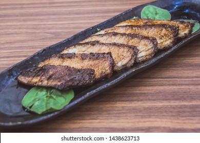 Side dish Kurobuta Hoho Yaki Grilled Iberico Pork Jowl served on spinach leaves